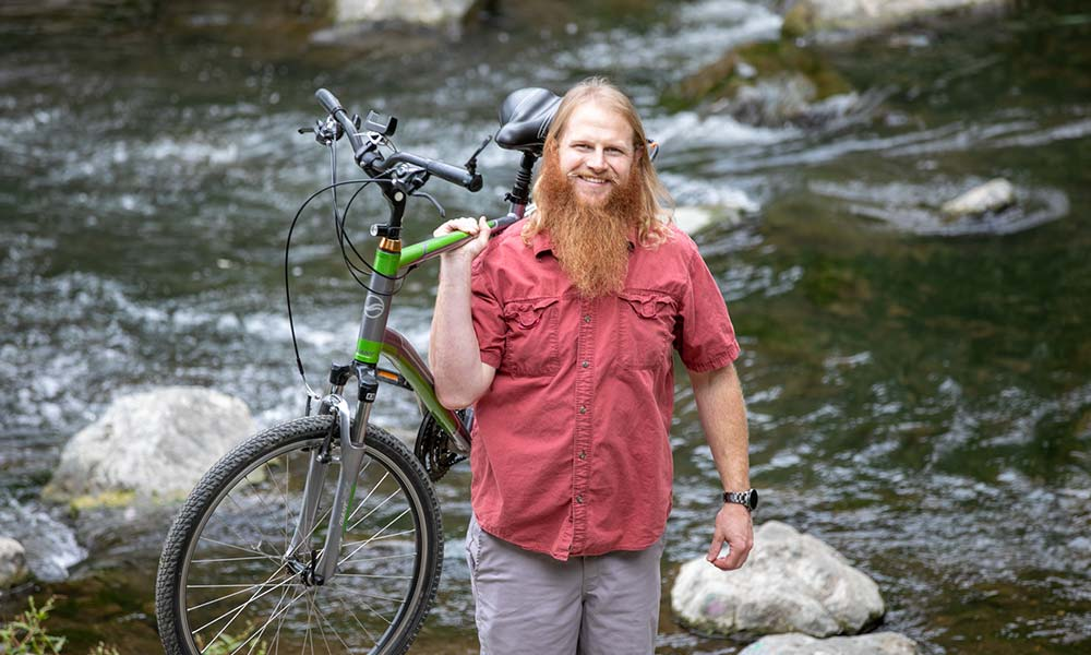 Steve standing in front of a stream of water, carrying a bike